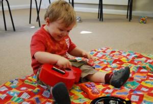 Toddler explores ukulele